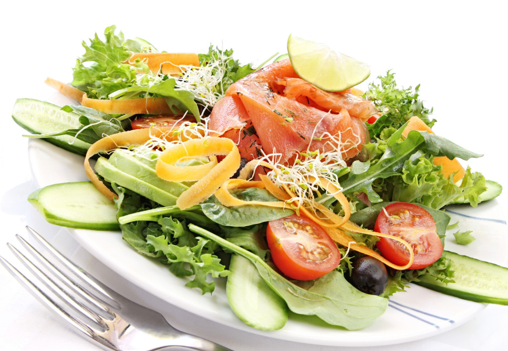 Smoked salmon salad, with mixed greens, cherry tomatoes, avocado, black olives, carrots, sprouts, cucumber, and lime.  Delicious healthy eating.